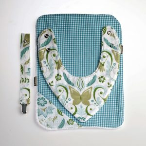 Un regalo seguro para el recién nacido que consiste en un tres en uno: babero, toallita y chupetero.